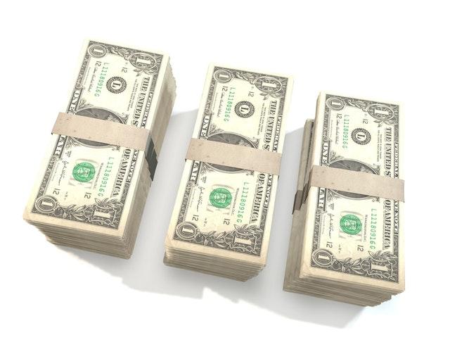 tři balíčky dolarových bankovek.jpg